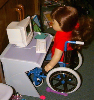 Doll working at her computer desk.